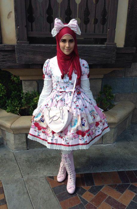 Chica usando un vestido de color blanco con flores rojas y un hijab en la cabeza y una bolsa blanca cruzada sobre el pecho