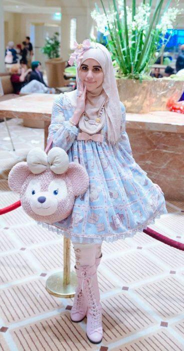 Chica usando un vestido de color azul pastel hasta la rodilla, una bolsa de un oso y un hijab color rosa