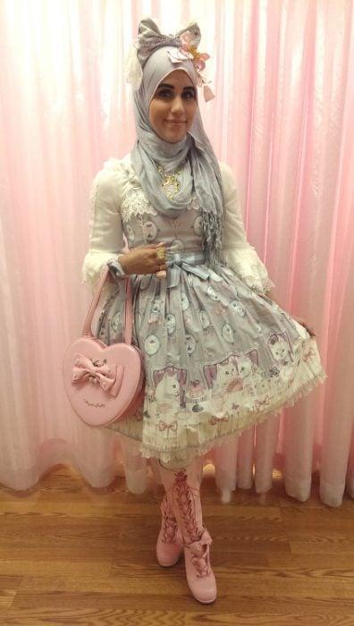 Chica usando un vestido gris con rosa de flores con un bolsa rosa y un hijab de color gris