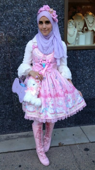 Chica musulmana usando un vestido de color rosa con accesorios y bolsa de conejo y un hijab en la cabeza
