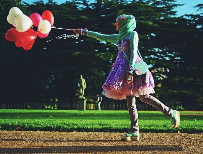 Chica usando pantalon y sobre ellos un vestido de color morado y un hijab de color verde