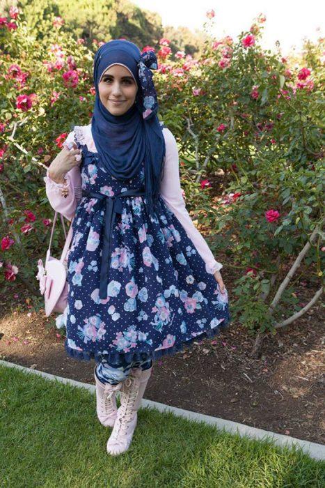 Chica usando un vestido de color azul con flores, suéter rosa y bolsa blanca con un hijab de color azul