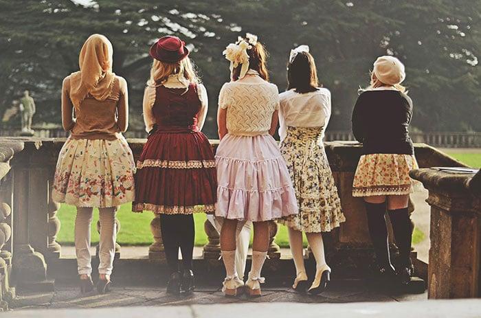 Chicas usando vestidos cortos hasta la rodilla de colores mientras están recargadas en un balcón