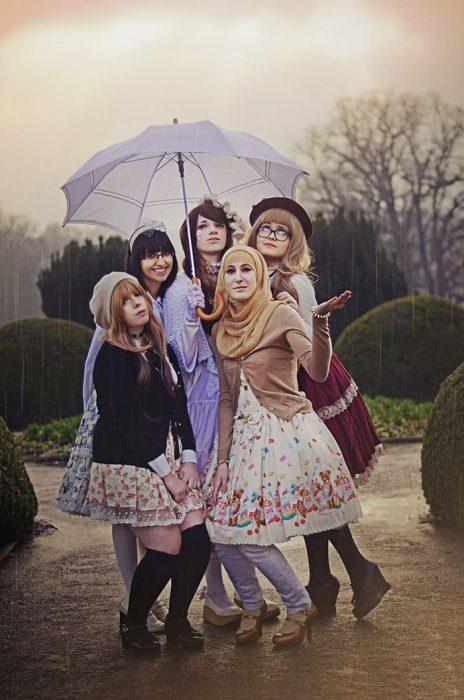 Chicas usando vestidos cortos blancos con flores de colores mientras sostienen un paraguas bajo la lluvia