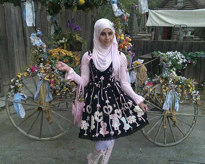 Chica usando un vestido de color negro con corazones y flores y un hijab de color rosa mientras esta parada frente a una bicicleta