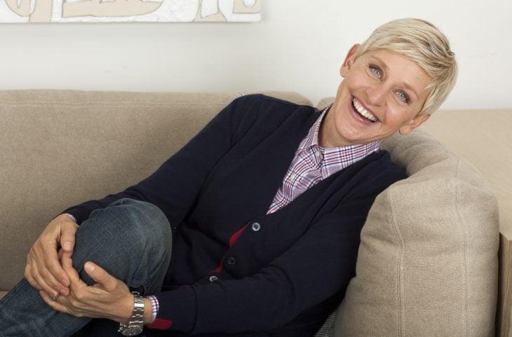 Conductora de televisión Ellen deGeneres sentada en un sofá riendo