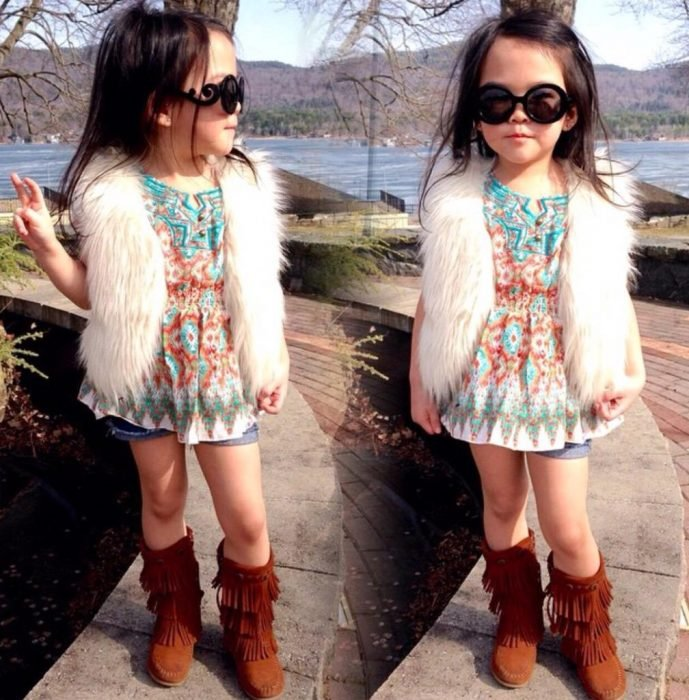 Niña usando un chaleco con short botas y lentes de sol