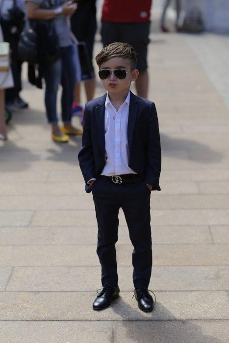Niño fashionista usando un traje parado en la calle enviando una foto