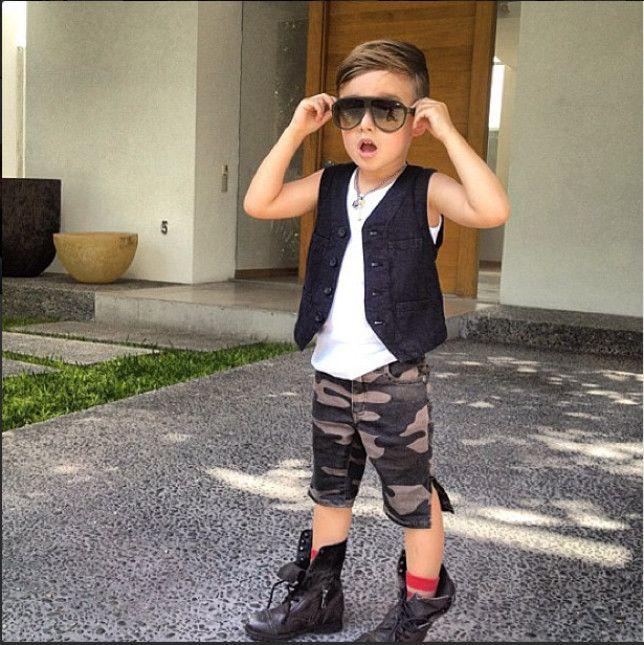 Niño usando un pantalón de militar corto, botas y chaleco parado a fuera de una casa