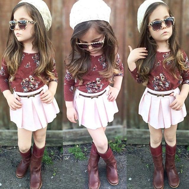 27b7c6313 Niña usando un falda rosa con blusa y botas rojas recargada sobre una pared