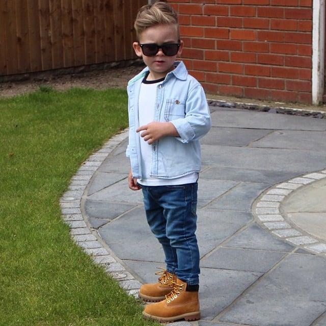 88a0e8776183b Niño vestido con pantalón y camisa de mezclilla posando para una fotografía