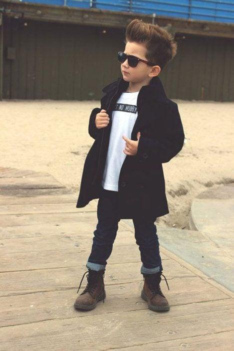 Niño usando una gabardina, botas y pantalón de mezclilla posando para una foto