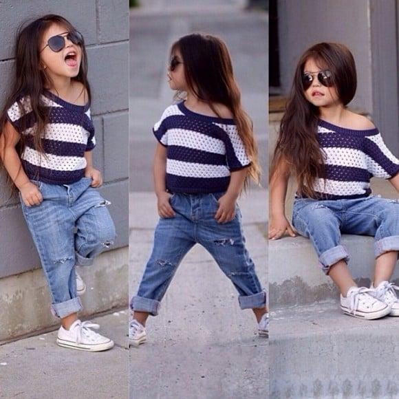 Niña de cabello largo usando una blusa a rayas con pantalón de mezclilla y tenis