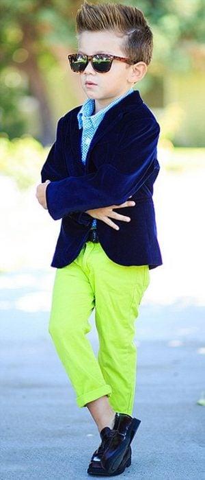 NIño con pantalón neón y saco azul y lentes obscuros posando para una fotografía