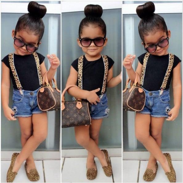 Niña usando un short blusa negra zapatos de leopardo y bolsa
