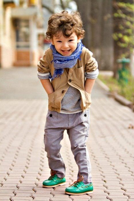 Bebé usando una chaqueta bufanda y pantalón gris parado en la calle