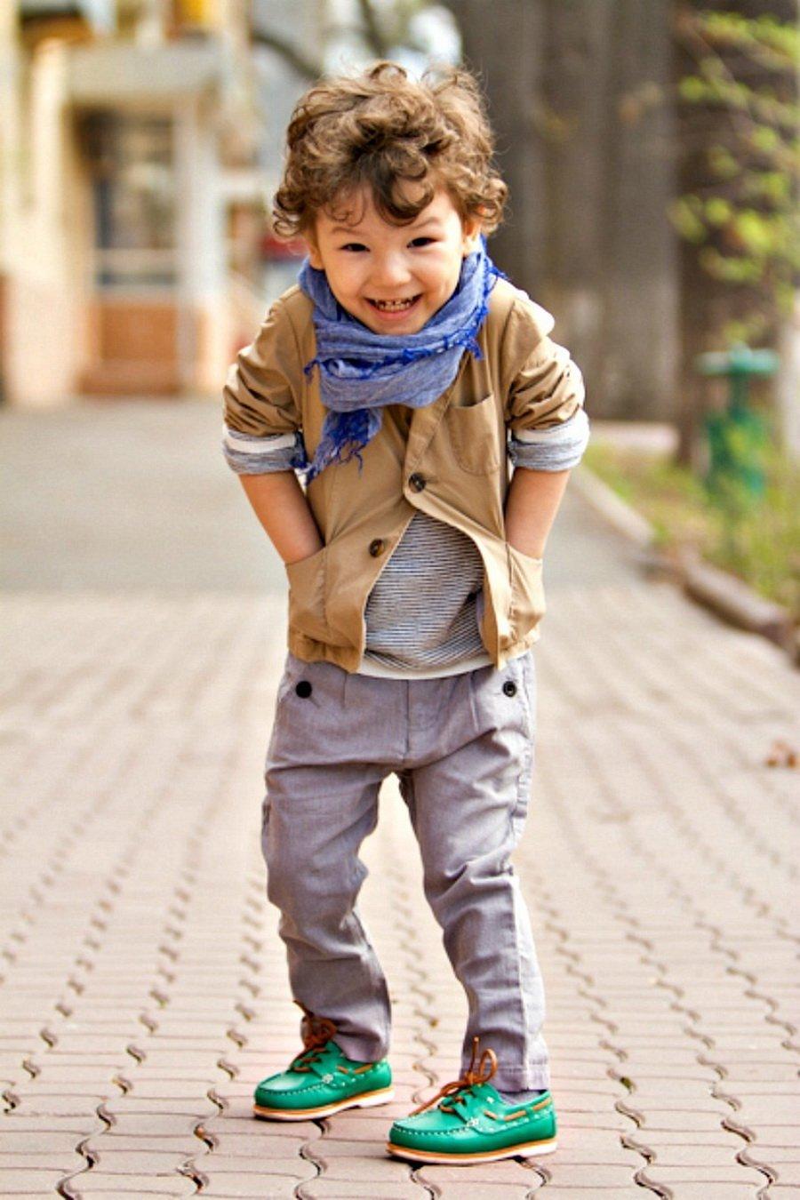 f3f06b8bf98e3 Bebé usando una chaqueta bufanda y pantalón gris parado en la calle