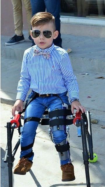 Niño fashionista con discapacidad sentado sobre una silla de ruedas