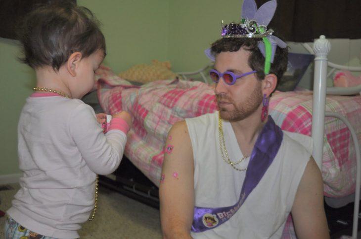 Niña poniendole estampas en el brazo su papá