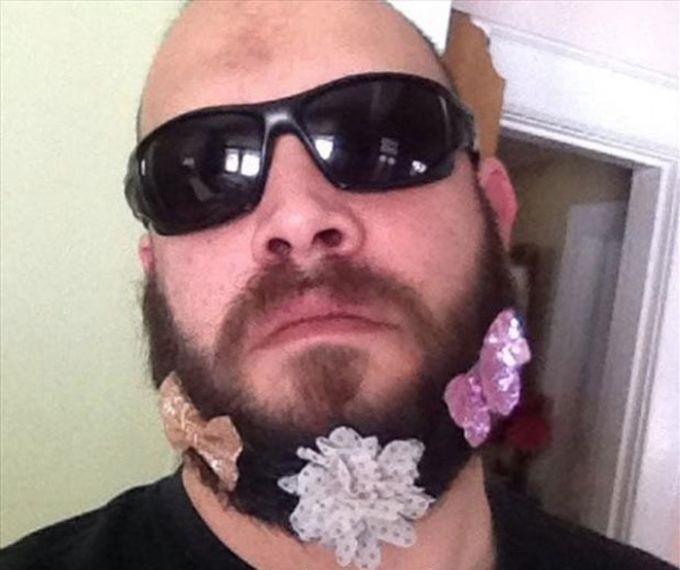 Hombre con barba y usando lentes con moños de niña puestos en su barba