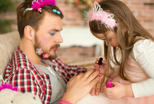 Niña pintandole las uñas a su papá y poniendole broches en el cabello