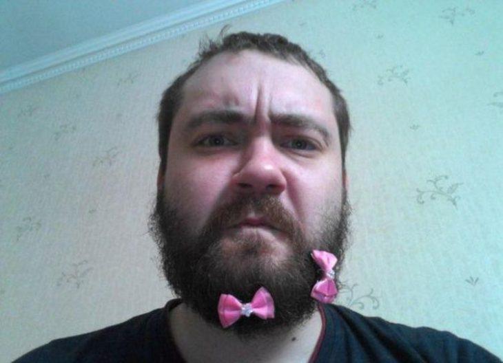 hombre con camisa negra usando moños en la barba