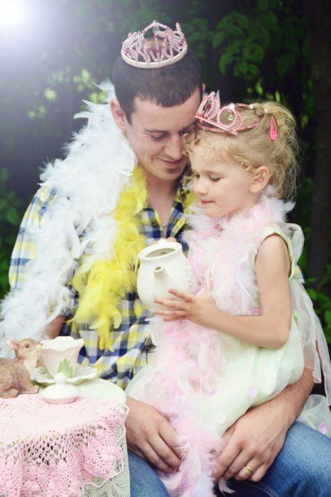 papá junto a su hija usando una boa de plumas mientras juegan al té