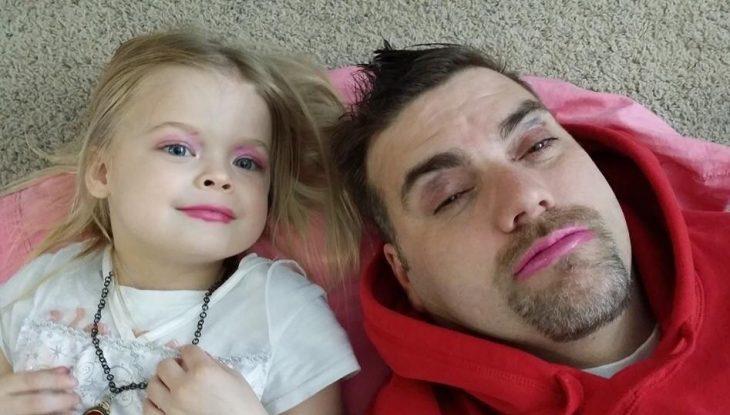 Papá junto a su hija reostados en la alfombra mientras muestran sus maquillajes