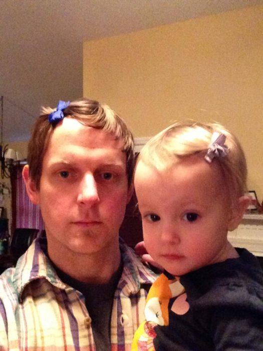 padre e hija luciendo iguales con moños en la cabeza