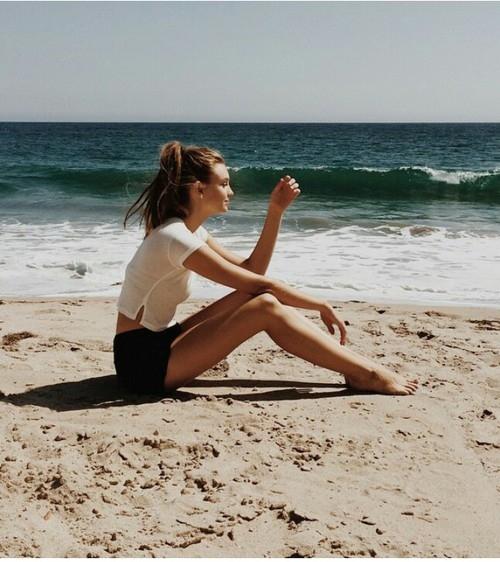 Chica sentada en la playa pensando