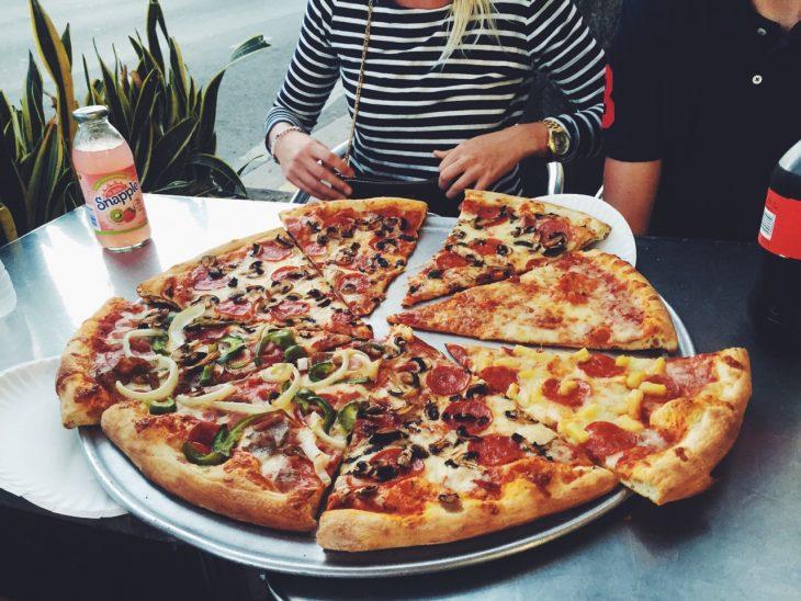 Chica frente a una gran pizza