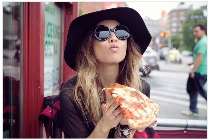 Chica con sombrero comiendo pizza