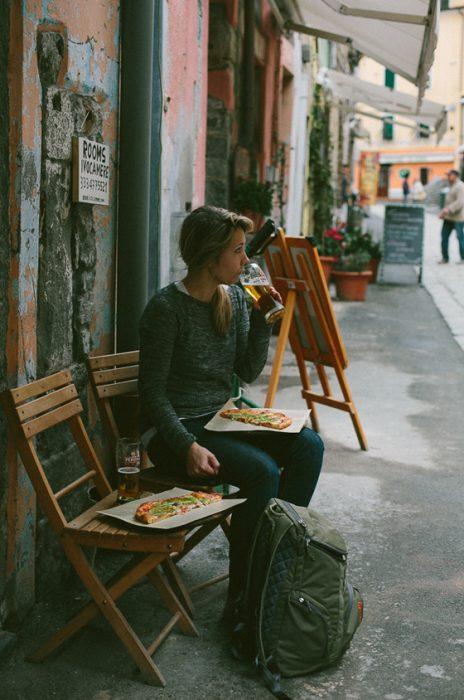 chica comiendo pizza en la calle