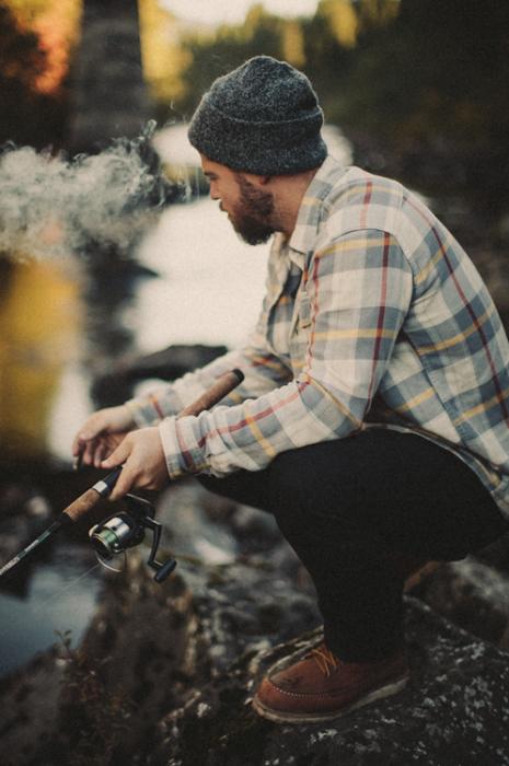 Chico pescando a la orilla de un río