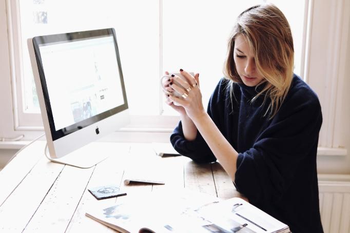 Chica frente a una computadora tomando café