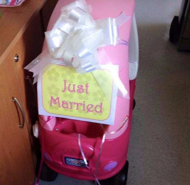 Carro de juguete con un moño y un letrero que dice recién casados