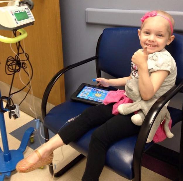 Niña enferma de cancer sentada en una silla recibiendo un tratamiento de quimioterapia