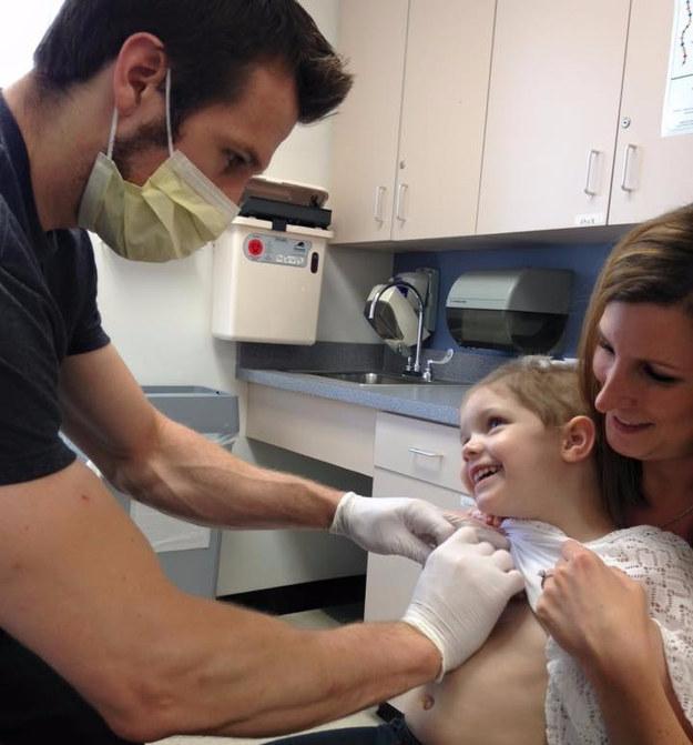 enfermero colocándole una inyección a una niña