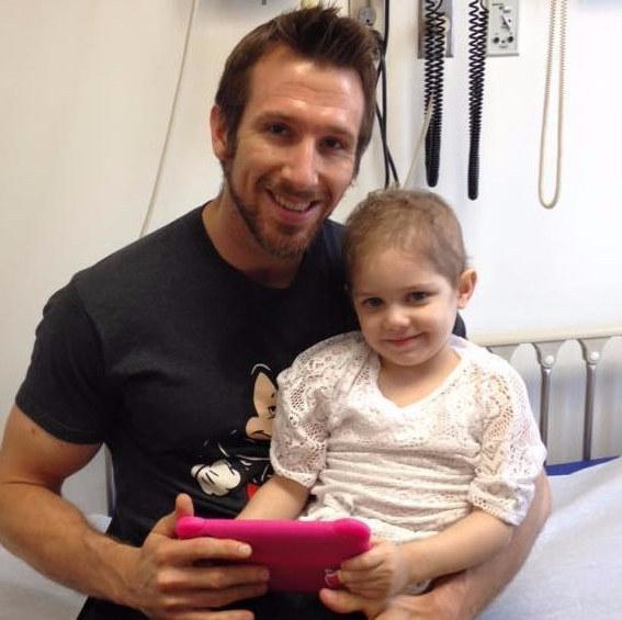 Enfermero sosteniendo a un niña enferma de cáncer mientras ven una tablet