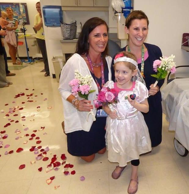 Niña vestida de novia junto a una enfermera y una doctora