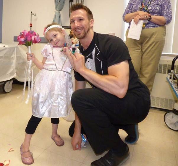 niña vestida de novia junto a un enfermero vestido con una camisa de esmoquin
