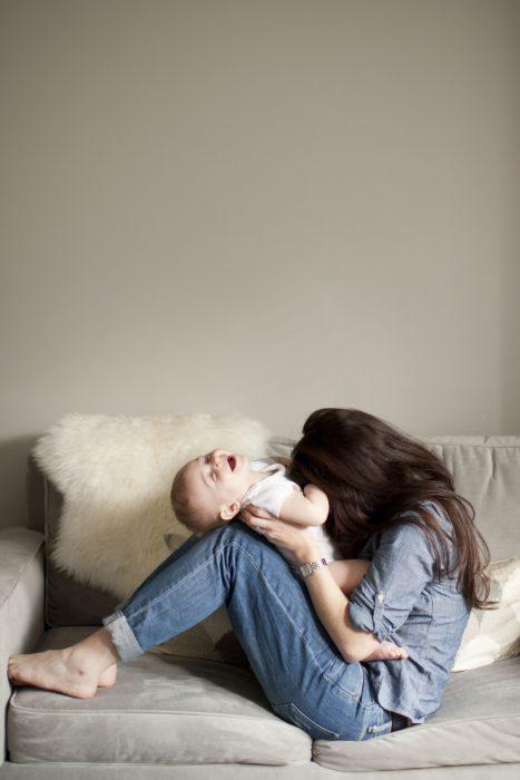 Chica y bebé en el sillón riendo