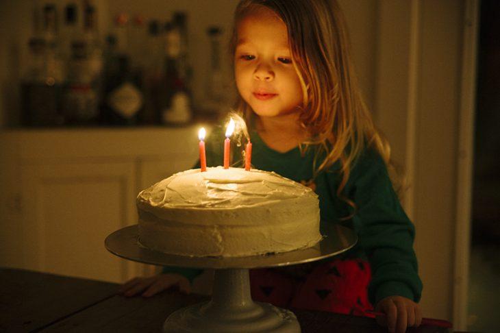niña apagando velitas de pastel