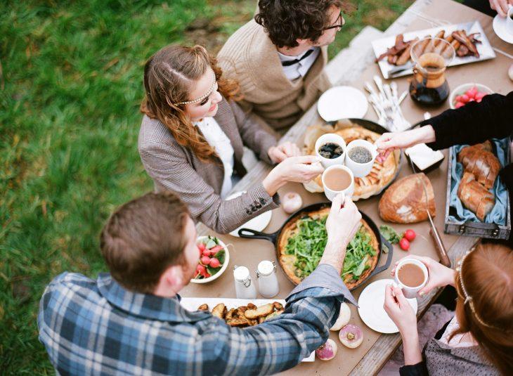 Reunion familiar de personas que estan desayunando en el jardín de una casa