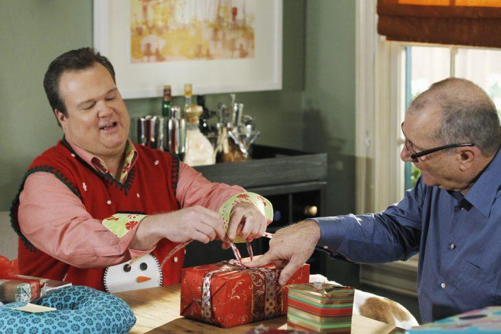 Hombres envolviendo un regalo sobre la mesa de la cocina