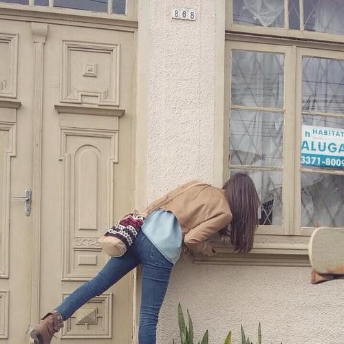 Chica asomándose por la ventana de una casa