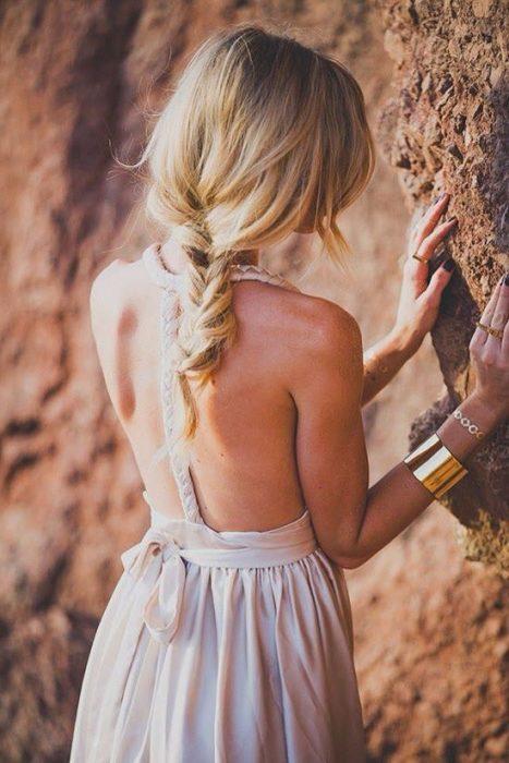 Chica sosteniéndose de una roca mientras esta de espaldas mostrando su trenza
