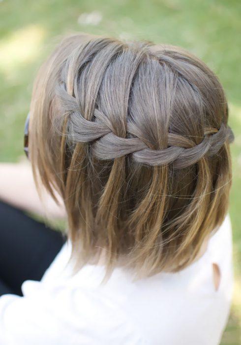 Chica con el cabello corto luciendo una trenza mientras esta de espaldas