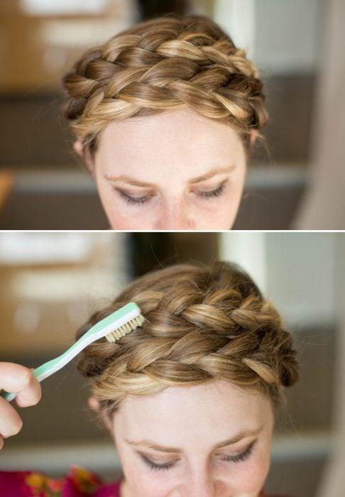 Chica texturizando su corona de trenza con un cepillo de dientes