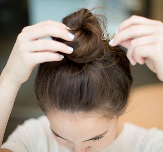 Chica colocándose un broche de resorte en el cabello